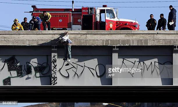 Mexican firemen stare at the body of a man hanging from a bridge in Tijuana northwest Mexico in the border with the US on December 14 2009 The north...
