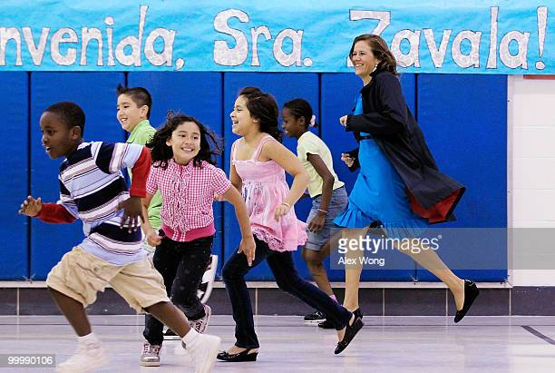 Mexican first lady Margarita Zavala runs with second graders during a physical education class as she visits New Hampshire Estates Elementary School...