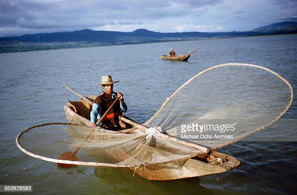 A mexican fishermen paddles his canoe as the goes butterfly net fishing in Patzcuaro Michoacan Mexico