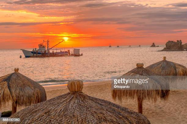 mexican fishing boat against the sun and sunset - halbinsel niederkalifornien stock-fotos und bilder