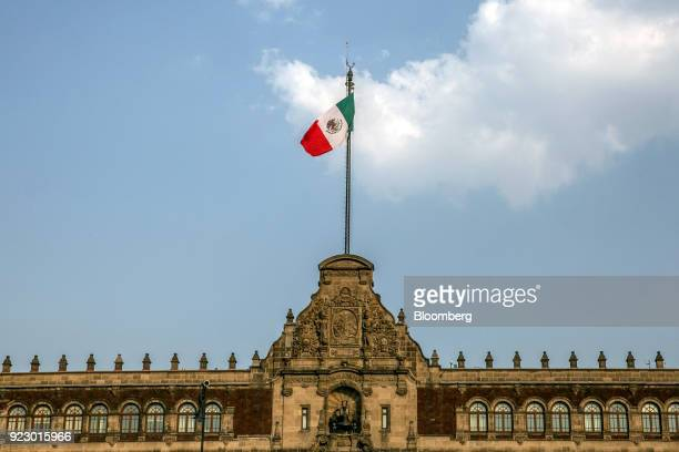 Mexican flag flies outside the National Palace building in Mexico City, Mexico, on Friday, Feb. 16, 2018. The National Institute of Statistics and...