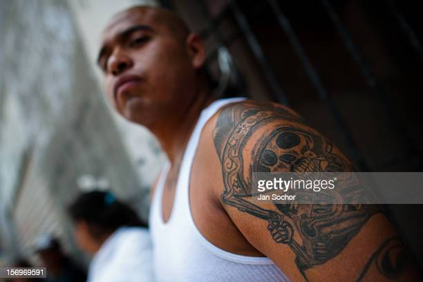 A Mexican follower of Santa Muerte shows his tattoo during the pilgrimage in Tepito a rough district of Mexico City Mexico 1 May 2011 The religious...