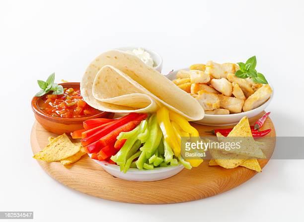 mexican food: meat, tortilla, nachos, salsa, sour cream and pepp