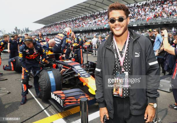 Mexican football player Jonathan Dos Santos poses for a photo on the grid with the Red Bull Racing team before the F1 Grand Prix of Mexico at...