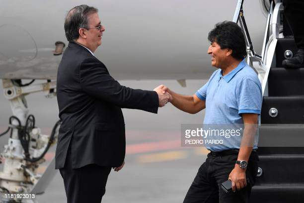 TOPSHOT Mexican Foreign Minister Marcelo Ebrard shakes hands with Bolivian exPresident Evo Morales upon his arrival in Mexico City on November 12...