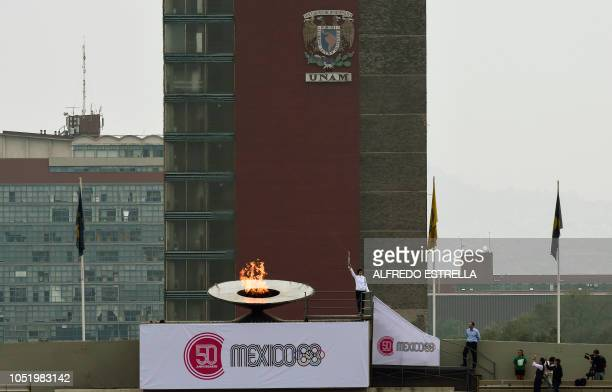 Mexican former Olympic track and field athlete Enriqueta Basilio symbolically lights the olympic cauldron during the ceremony to mark the 50th...