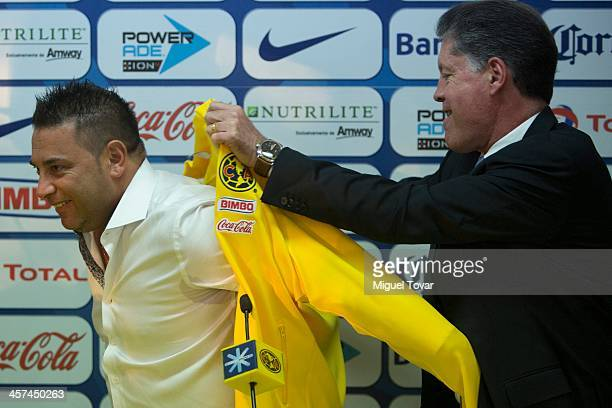 Mexican former player Ricardo Pelaez helps Antonio Mohamed to wear an America's jacket during Mohamed's presentation as new coach of Mexican team...