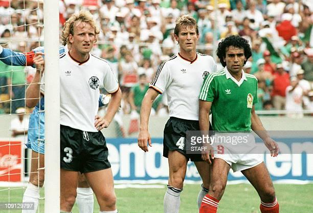 Mexican forward Hugo Sanchez standing near the goal cage waits for a corner kick surrounded by West German defenders Andreas Brehme and Karlheinz...