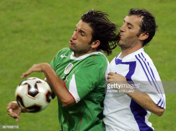Mexican forward Jose Fonseca vies with Greek midfielder Angelos Basinas during the Confederations cup football match Greece vs Mexico 22 June 2005 at...