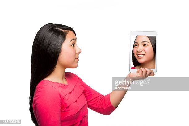 Mexican girl looking at her photo on digital tablet