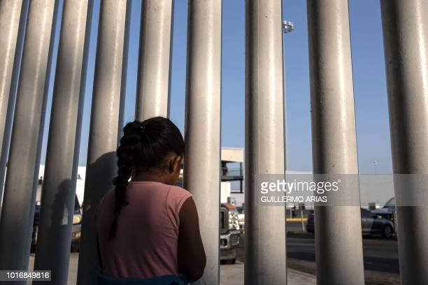 A Mexican girl who seeks for asylum in the US looks through a fence at El Chaparral port of entry in Tijuana Baja California state Mexico on August...
