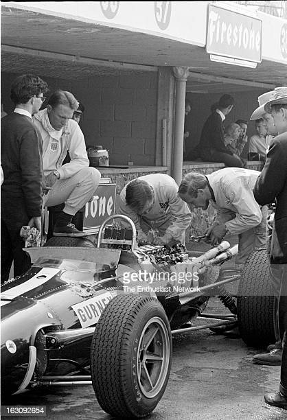Mexican Grand Prix AAR founder and driver Dan Gurney stands in the pits with his crew and mechanics as they work on his Climax powered Eagle T1G...