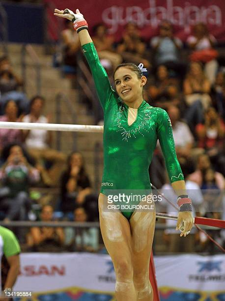 Mexican gymnast Elsa Garcia waves at the crowd finalizing her routine in the parallel bars to win the bronze medal tied to fellow country woman...