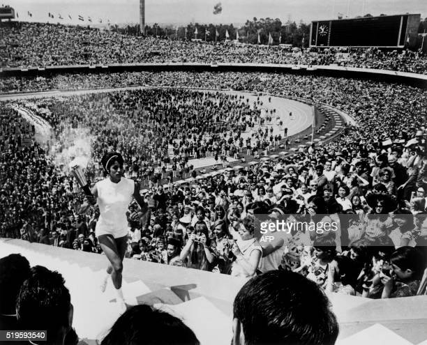 Mexican hurdler Norma Enriqueta Basilio de Sotelo, the first woman to light the Olympic flame, carries the torch during the opening ceremony of the...