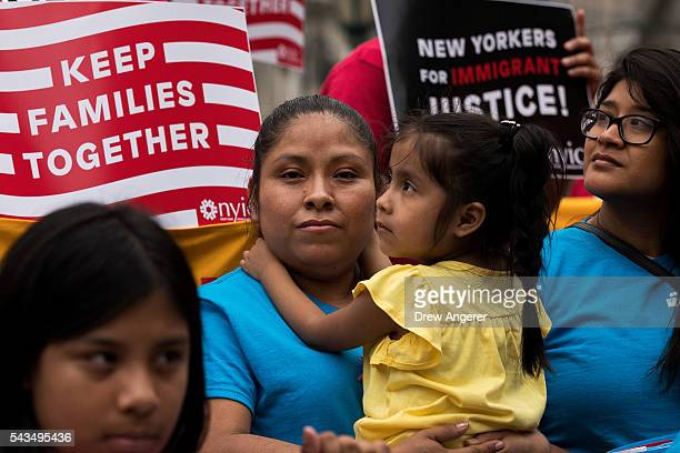 Mexican immigrant Nieves Ojendiz holds her 4year old daughter Jane as she attends an immigration reform rally with members and supporters of the New...