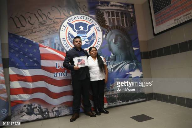 Mexican immigrant poses for photos with his mother while holding a US citizenship certificate at a naturalization ceremony on February 2 2018 in New...