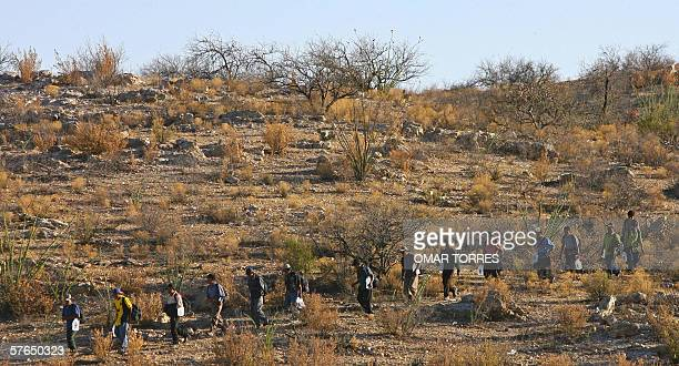Mexican immigrants carrying bottles of water attempt to cross the MexicoUS border illegally from Sasabe in the state of Sonora into the Arizona...