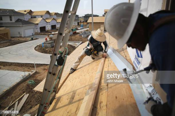Mexican immigrants work on a housing construction site on May 3 2013 in Denver Colorado The resurgent housing market has helped drive down...