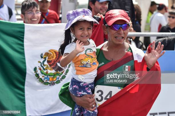 Mexican Jose Ojeda poses for photographers with his daughter after winning the Men's 50 Km Race Walk during the 2018 Central American and Caribbean...