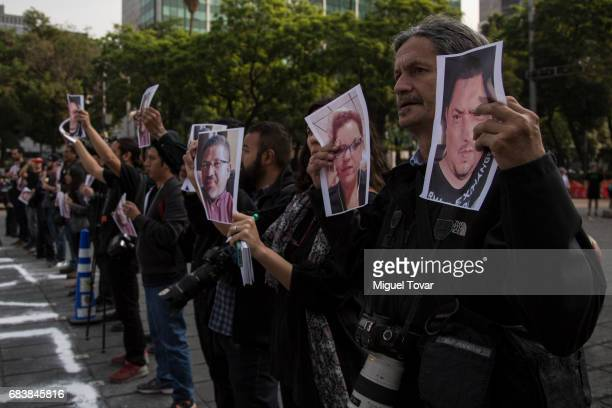 Mexican journalists display portraits of their murdered colleagues during a demonstration to draw attention to the latest wave of killings of...
