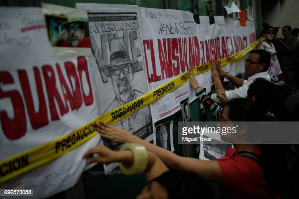 Mexican journalists tape signs to a wall during a demonstration to end violence against journalism in Mexico outside the Palacio de Bellas Artes on...
