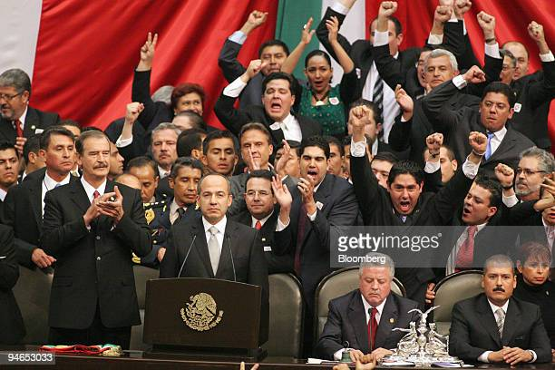 Mexican Legislators cheer and yell as Mexican President Felipe Calderon center takes the oath of office with former President Vicente Fox left at...