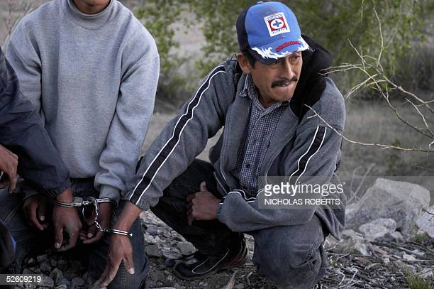 Mexican Lorenzo Jimenez of Queretaro looks down the train tracks while handcuffed to two other Mexican migrants after being apprehended aboard a slow...