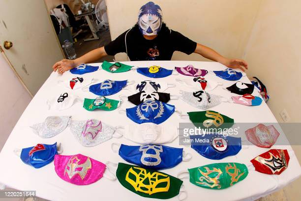 Mexican Lucha Libre wrestler, 'El Hijo del Soberano' shows face masks from different Mexican Lucha Libre fighters on April 21, 2020 in Torreon,...