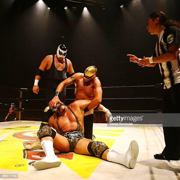 Mexican Lucha Libre Wrestler El Hijo Del Solitario moves to take off the mask of The Silver King as El Hijo De Cien Caras stands watching at the...