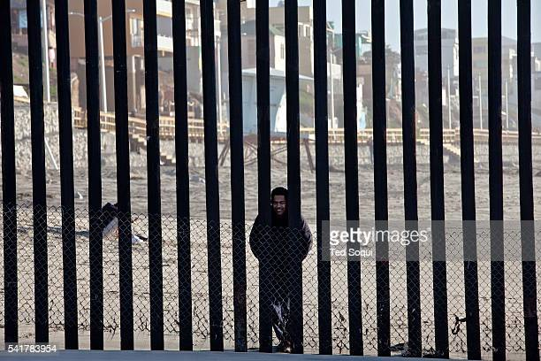 A Mexican man looks through the border fence from the Mexico side of the border fence The rusty border fence that separates the US and Mexico extends...