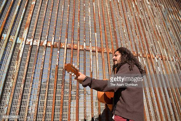 A Mexican man performs guitar while a man in the US side of border performs violin after the on January 29 2017 in Tijuana Mexico US President Donald...