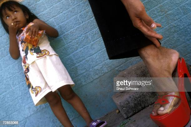 Mexican man tries on a red shoe while a young girl watches in Juchitan Mexico October 1 2002 In the southern Mexican town of Juchitan of roughly 85...