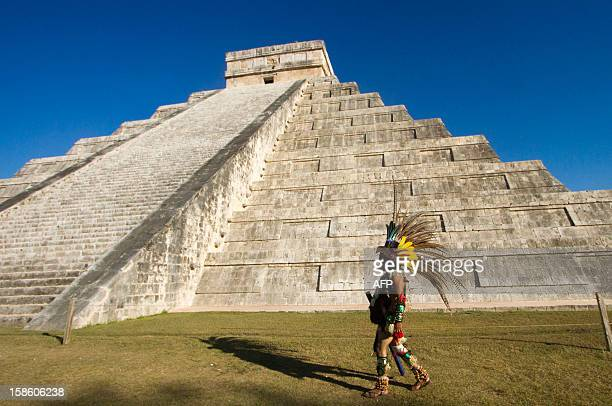 A Mexican man wearing a prehispanic costume walk next to the kukulkan pyramid at the Chichen Itza archaeological park in Yucatan state Mexico on...