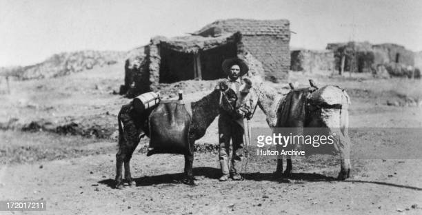A Mexican man with a wide brimmed hat stands holding two donkeys carrying packs in front of a brick building Mexico circa 1910