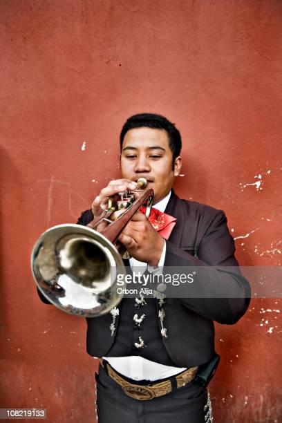 hombre tocando trompeta mariachis mexicana contra la pared - mariachi fotografías e imágenes de stock