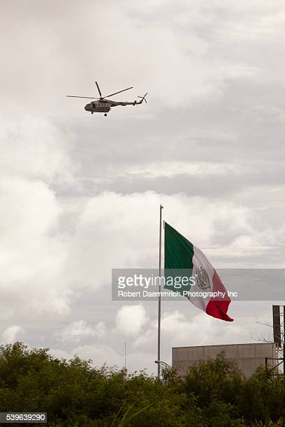 A Mexican Marine military helicopter patrols the Rio Grande River as it flies past a large Mexican flag at the US border with Brownsville Texas on...