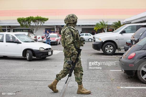 A Mexican marine patrols a commercial plaza after looting in Veracruz City Mexico on Saturday Jan 7 2017 Mexico's National Association Of Retail And...