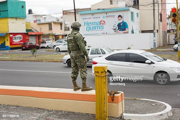 A Mexican marine stands guard at a commercial plaza after looting in Veracruz City Mexico on Saturday Jan 7 2017 Mexico's National Association Of...