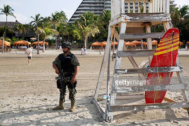 A Mexican Marine stands guard on the beach in Acapulco Mexico on Friday March 20 2015 Passenger traffic to Mexico from abroad rose more than 10...