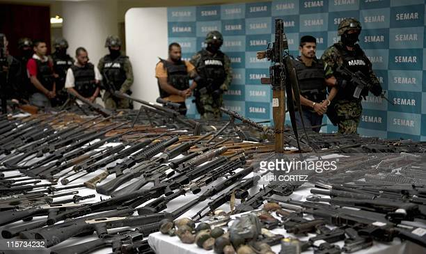 Mexican marines escort five alleged drug traffickers of the Zeta drug cartel in front of an RPG-7 rocket launcher, hand grenades, firearms, cocaine...