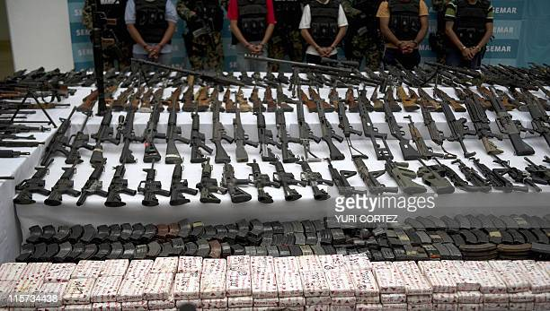 Mexican marines escort five alleged drug traffickers of the Zetas drug cartel in front of hand grenades firearms cocaine and military uniforms seized...