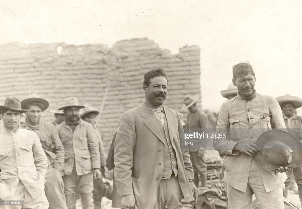 Mexican military commander Pancho Villa (1878 - 1923) (center) stands with his men, late 1910s.