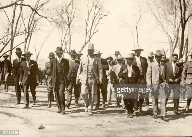 Mexican military commander Pancho Villa walks with a group of his men all in suits and most in hats mid 1910s