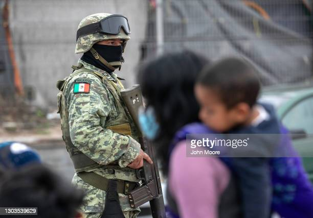 Mexican military police stand guard as Central American immigrants wait at migrant camp for entry into the United States on February 22, 2021 in...