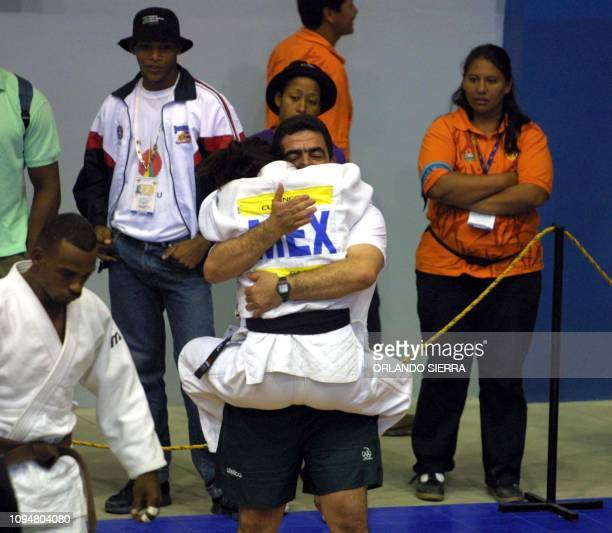 Mexican Miriam Ruiz embraces a member of her delegation 29 November 2002 after winning the gold medal in the judo competition category of 63kg of XIX...