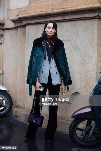 Mexican model Cristina Piccone wears a green shearling bomber jacket over a gray glenn check blazer a red scarf and holds a purple purse during Milan...