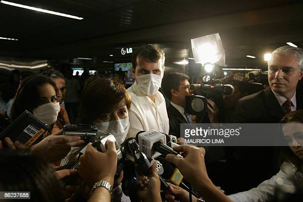 Mexican national Charo de la Parra speaks with journalists wearing masks to ward off infection by the new multistrain swine flu virus next to her...