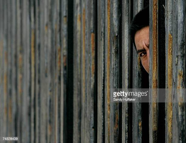Mexican National peers through the US Mexico border wall June 10 2007 in San Ysidro California President Bush will meet with key Senators this week...