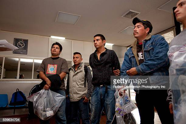 Mexican nationals who were caught in the United States after illegally entering the country arrive at the immigration checkpoint directly across the...