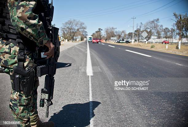 A Mexican Navy member stands guard in a highway in the state of Mexico near the capital Toluca on January 29 2013 According to local authorities000...